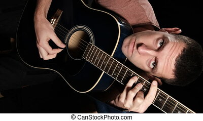 Vertical video: Young man plays an acoustic guitar on a black background. Sitting on a chair, a blogger guitarist is filming himself for social networks. Studio shot. 4K. 400mbit, 10bit, All-Intra
