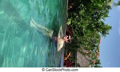 Vertical video. Young man in sunglasses swimming in a private pool at luxury tropical villa at vacation.