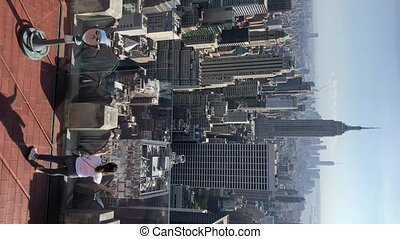 Vertical video. Young woman using scope at observation deck...