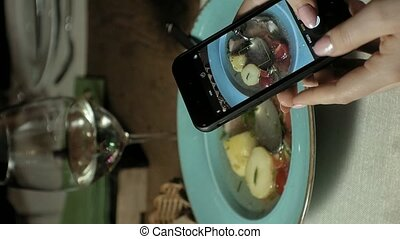 Vertical video.Vertical video. woman photographs food on the...