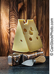 vertical view big piece of milk maasdam cheese on little cutting board and knife old wooden background
