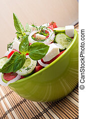 Vertical view close-up on a green bowl with a salad