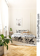 Vertical view of a bright bedroom interior with a big bed standing on a herringbone wooden floor. Black and white bedding and a breakfast tray on the bed. Real photo