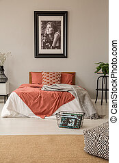 Vertical view of bedroom with king size bed with pillows, duvet and blanket and poster in frame on the wall, real photo with mockup
