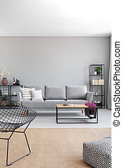 Vertical view of elegant grey living room with comfortable couch, metal shelves and wooden coffee table, real photo with copy space