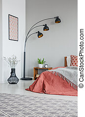 Vertical view of grey blanket on bed with cushions in bedroom interior with lamp and plants, real photo