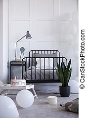 Vertical view of metal bed with grey bedding and white pillow on the empty white wall, real photo with copy space