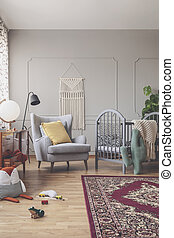 Vertical view of mid century baby room with rustic rug, comfortable grey armchair and wooden crib with patterned bedding