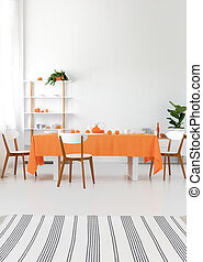 Vertical view of modern interior. Long dining room table with chairs. White walls and floor, orange details. Real photo concept
