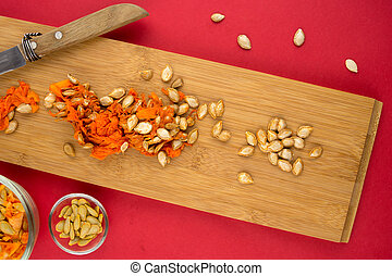 Vertical view of pumpkin flesh and seeds on cutting board