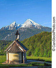 Vertical view of small chapel and snowy summit of Watzmann mountain