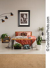 Vertical view of stylish bedroom with king size bed with rust colored bedding , poster on the wall and green plant, real photo