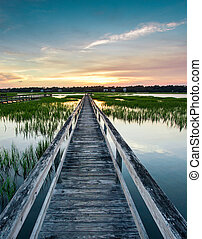 vertical view of sunset over coastal waters with a very long wooden boardwalk