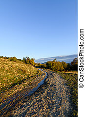 Vertical view over rural road in autumn landscape. Mountain rural road with water and mud, blue sky at the horizon and white clouds.