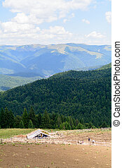 Vertical view with sheepfold and mountains. Wooden sheepfold in Carpathians near mountain range.