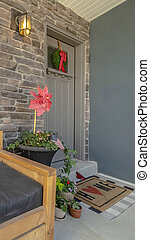 Vertical Wooden bench with pillows at the porch of home with glass paned gray front door