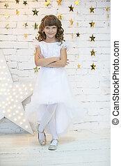 Vertically elegant child in a white dress. Seven year old girl model