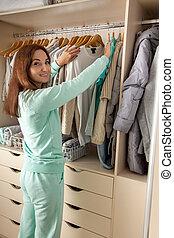 verticalmente, camisetas, plataformas, armário, dela, clothes., branca, mulher, bonito, basket., cima, dobrado, jovem, roupas, storage., pendura
