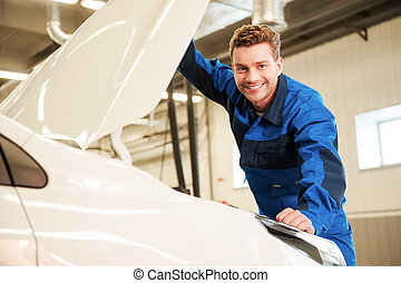 vertrauen, zu, professionals., hübsch, junger mann, in, uniform, untersuchen, auto, und, lächeln, während, stehende , in, werkstatt