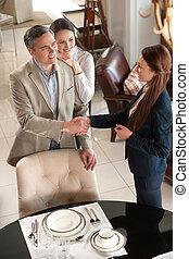 vervaardiging, een, deal., vrolijk, van middelbare leeftijd, paar, staand, in, de opslag van het meubilair, terwijl, man, schuddende hand, om te, omzet beamte