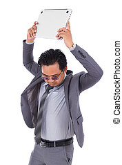 very angry business man is throwing away his laptop isolated on white background