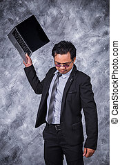 angry business man is throwing away his laptop