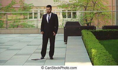 Very angry businessman walks down the street with a tablet. He drops the tablet and calm down.