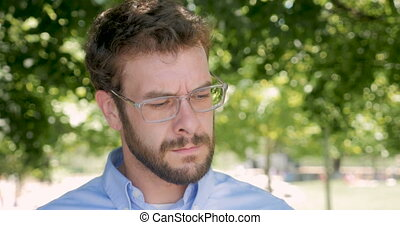 Very angry man pulls off his glasses and stares at the...