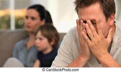 Very anxious man thinking about a bad thing while his family...