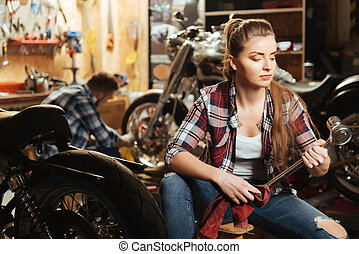 Very attentive woman working in the garage of her boyfriend