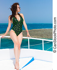 Very attractive young female standing on the yacht at a...