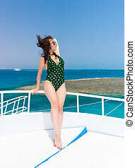 Very attractive young woman standing on the yacht at a sunny...