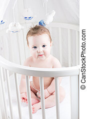 Very beautiful baby sitting in a white round crib