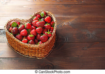 Very beautiful background with fresh strawberries in a wicker heart shaped wickerwork basket on old brown wooden background