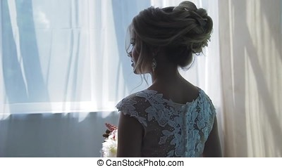 Very beautiful blonde with blue eyes in a white bride dress near a window with a bouquet of flowers