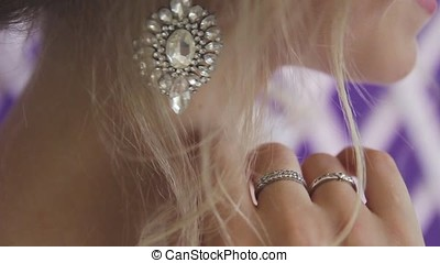 Very beautiful blonde with blue eyes in white bride dress on purple background in studio