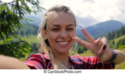 Very beautiful girl doing selfie in the mountains