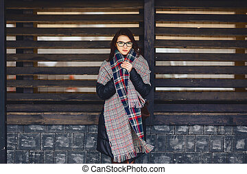 beautiful girl in eyeglasses and a scarf against a wooden wall