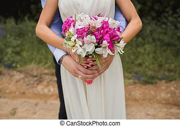 Very beautiful wedding bouquet in hands of the bride