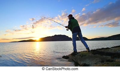 Very close rear view to working fisherman. Man check pushing bait and throws it far into the sea. Fisherman with fishing rod in his hand and  stands close to water against a beautiful sunset.