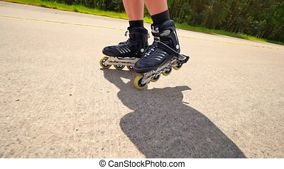 Very close up side view to working inline skates. Easy skating on the smooth  asphalt. Close up view to quick movement of black four wheels inline boots.