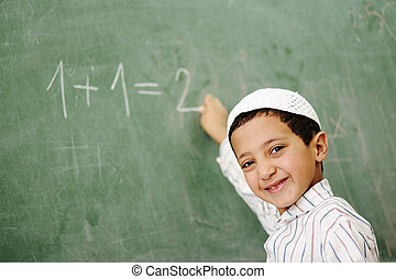 Very cute and positive kid smiling and writing on school board