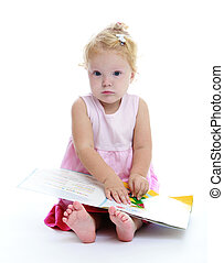 Very cute little girl reading a book sitting on the floor