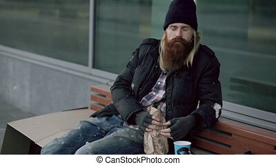 Very drunk homeless man show fuck you sign into the camera and sleeping while sitting on bench at the sidewalk