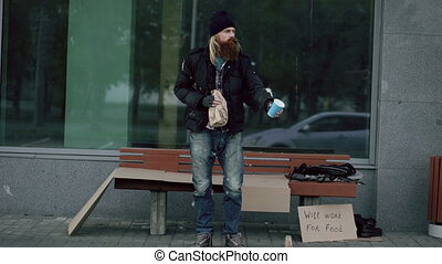 Very drunk homeless man with cardboard and alcohol sign beg...