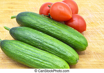 Very fresh green cucumbers and tomato on cutting board