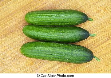 Very fresh green cucumbers on cutting board