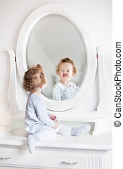 Very funny baby girl with curly hair looking at her...