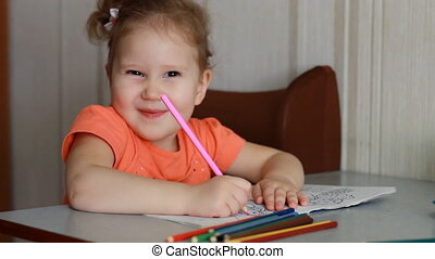 Very funny little girl draws with pencils, smiles and looks at the camera. The child is teasing