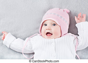 Very funny little girl in a pink knitted hat